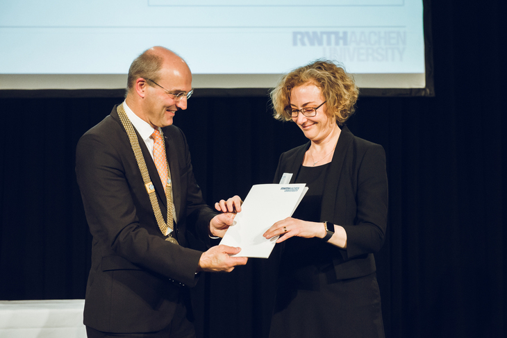 The rector of RWTH Aachen University presents a woman with an award